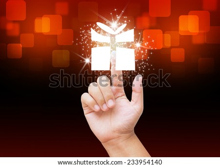 Hand pressing Christmas gift box buttons on holiday background - stock photo