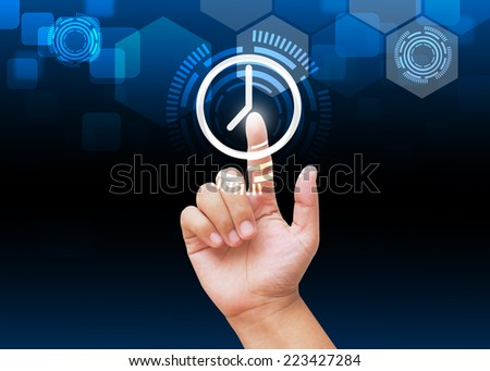 Hand pressing clock button on technology background  - stock photo