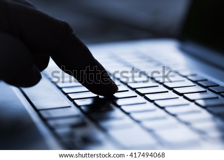 Hand pressing computer keyboard. Sillhouette effect - stock photo