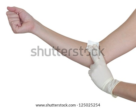 Hand pressing gauze on arm after administering an injection. Isolated on white. - stock photo