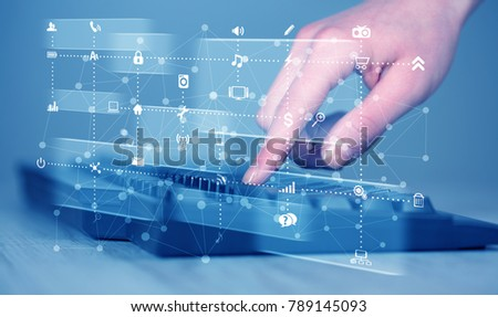 Hand pressing keyboard with high tech media icons and symbols
