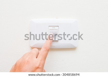 hand pressing light power switch on wall, electric
