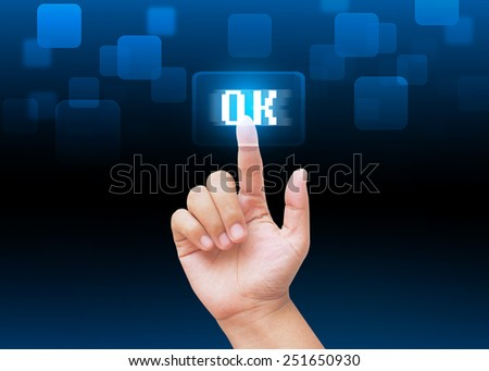 Hand pressing OK buttons with technology background  - stock photo