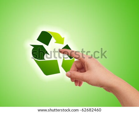 Hand pressing recycle icon on green gradient - stock photo