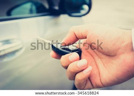 Hand pressing remote control car key, vintage tone - stock photo