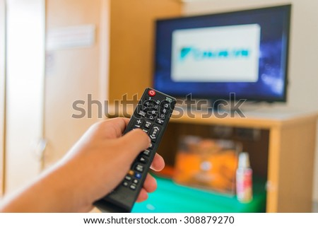 hand pressing remote control to the TV, television