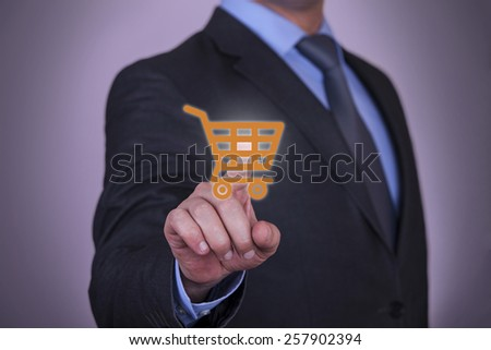 Hand Pressing Shopping Cart icon on screen - stock photo