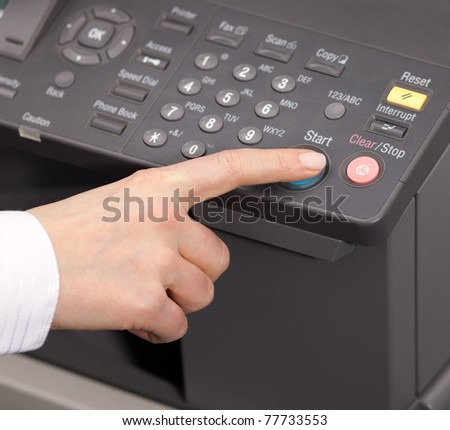 Hand pressing Start button on copy machine - stock photo