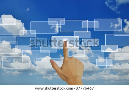 Hand pressing touchscreen button on the blue sky background - stock photo