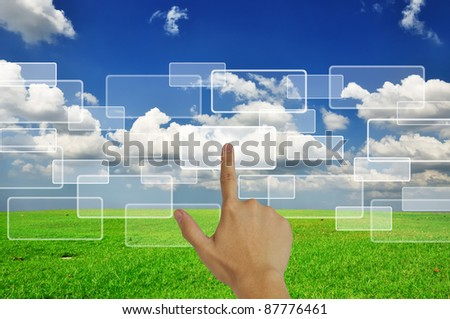 Hand pressing touchscreen button on the grassland and blue sky background - stock photo