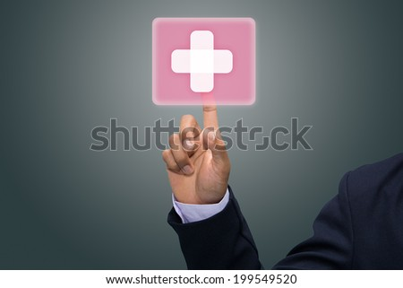 Hand pressing virtual button with first aid sign. - stock photo