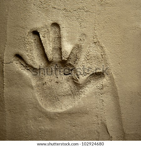 hand print on cement mortar wall with shadow relief - stock photo