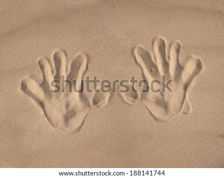 Hand prints on the sand  - stock photo