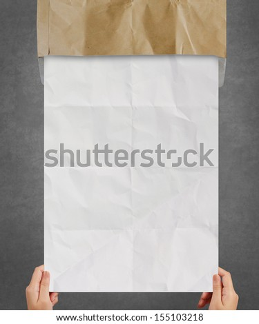 hand pulling crumpled paper from recycle envelope as concept background
