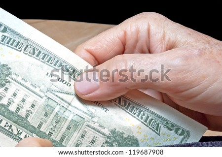 Hand pulling 20 dollar banknote from wallet - stock photo