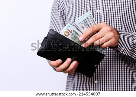 Hand pulling 100 dollars banknotes from wallet