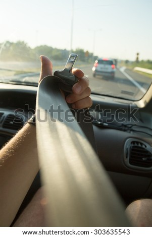 Hand pulling seat belt in the car