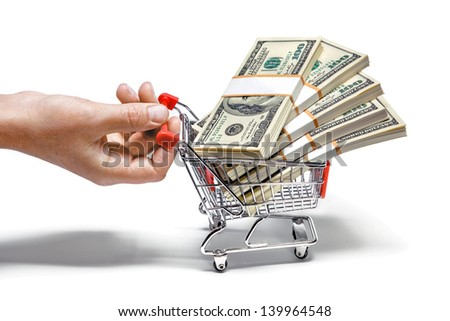 hand pulling shopping cart full of stacks of dollar bills isolated on white  - stock photo