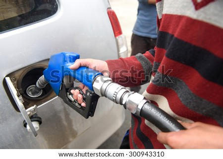 Hand Pumping Gasoline With Red Nozzle/ Refueling Again - stock photo