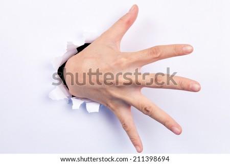 Hand punching through paper - stock photo