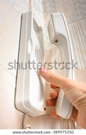 hand pushing a button on the intercom - stock photo