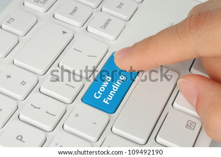 Hand pushing blue crowd funding button on keyboard - stock photo