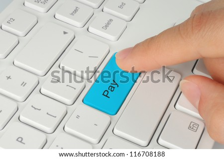 Hand pushing blue pay keyboard button
