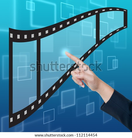 Hand pushing film button on a touch screen interface - stock photo