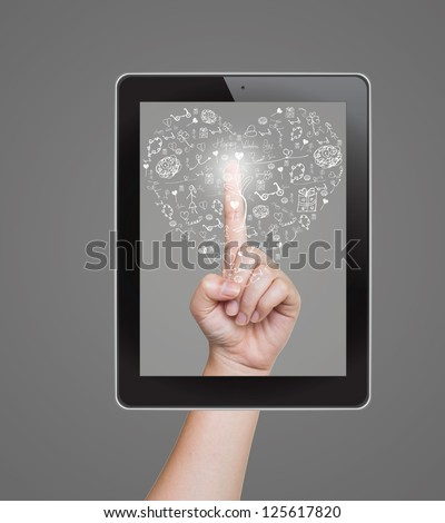 Hand pushing heart icon of tablet on a touch screen - stock photo