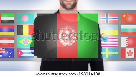 Hand pushing on a touch screen interface, choosing language or country, Afghanistan - stock photo