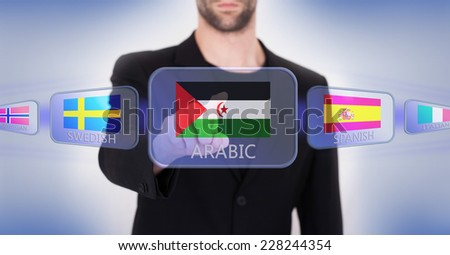 Hand pushing on a touch screen interface, choosing language or country, Western Sahara - stock photo