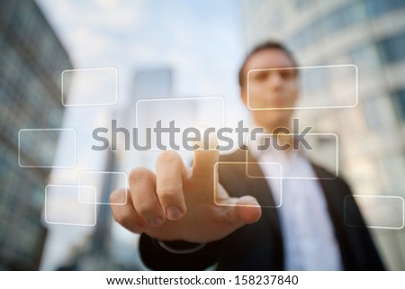 hand pushing on a touch screen interface on business buildings background - stock photo