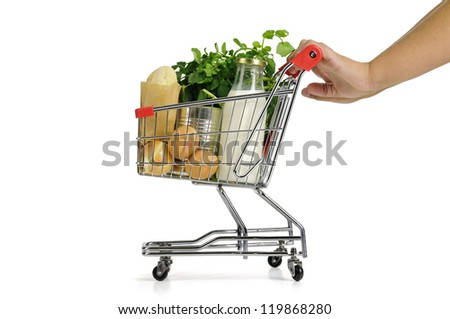 Hand pushing small shopping cart full with groceries  isolated in white - stock photo