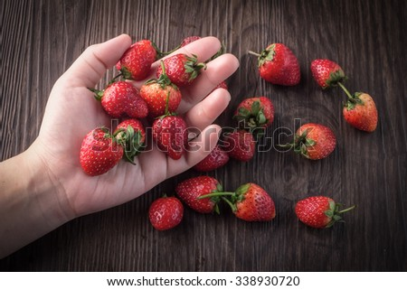 hand put a strawberry in her hand with wooden table background - stock photo