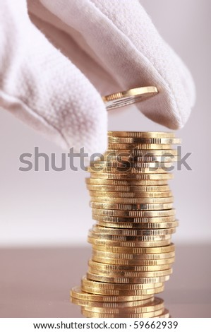 Hand put coin on coin-stack - stock photo