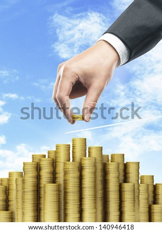 Hand put coins to money staircase and blue sky - stock photo