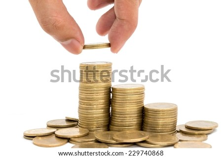 Hand put coins to stack of coins on white background . - stock photo