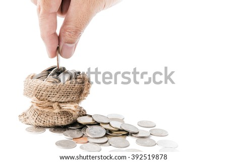 Hand put down money coin to sack isolated on white