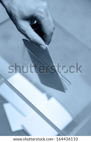 Hand putting a blank ballot inside the box, elections concept, blue tone - stock photo