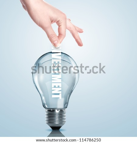 Hand putting a busines term into a light bulb - stock photo