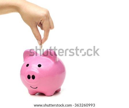 hand putting a coin into a pink piggy bank thinking of buying a new house and a car - saving money for future concept