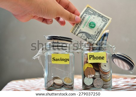 Hand putting a coin into glass jars with 'phone' text  - stock photo