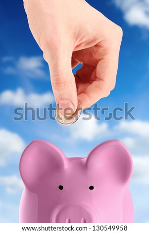 hand putting a coin into piggy bank - stock photo