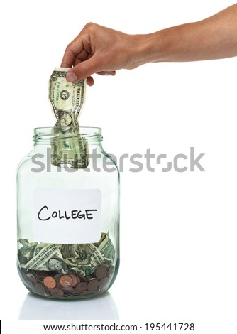 hand putting a dollar bill in a college savings jar - stock photo