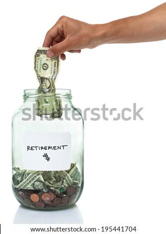 hand putting a dollar bill in a retirement savings jar - stock photo