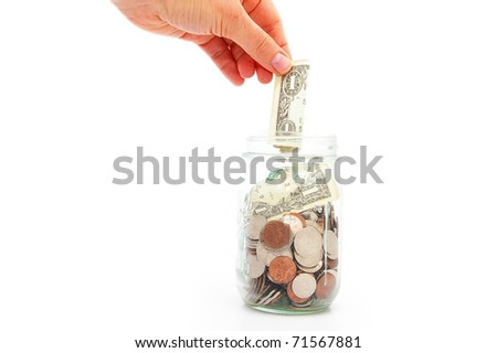 hand putting a dollar in a coin jar - stock photo