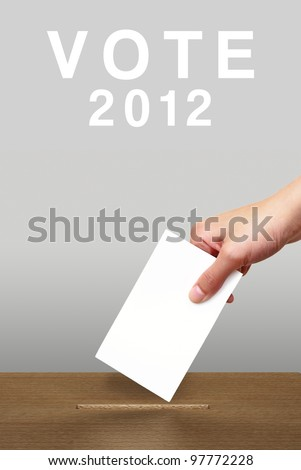 Hand putting a voting ballot in a slot of wooden box on white - stock photo