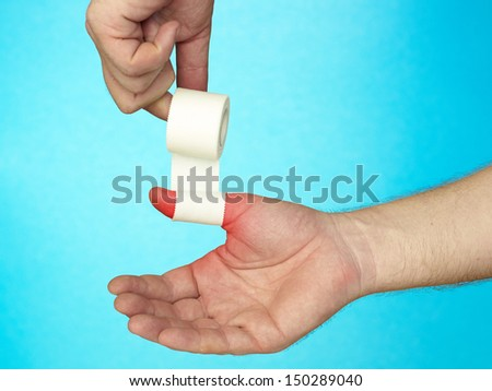 Hand putting Adhesive Bandage. On blue background. - stock photo