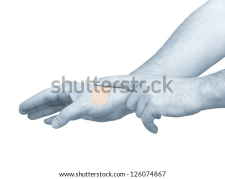 Hand putting Adhesive Bandage on hand. Concept photo with Color Enhanced skin with read spot indicating location of the pain.