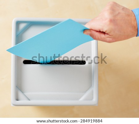 Hand putting ballot in ballot box during election - stock photo